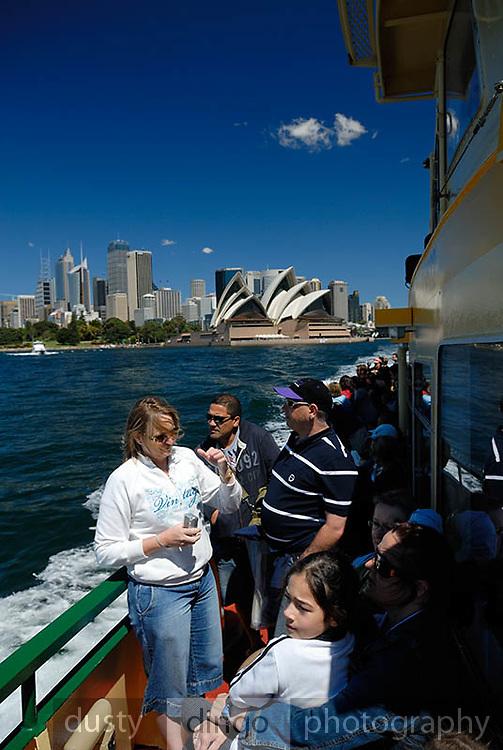 Passengers on deck of Sydney Ferry, Sydney Opera House and Circular Quay skyline in background. Sydney, Australia