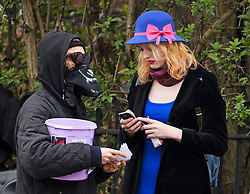 © Licensed to London News Pictures. 13/04/2018. London, UK. Transgender activist TARA WOLF (blue dress) is joined by a campaigner wearing a mask as she arrives at Hendon Magistrates' Court in London where she is currently on trial for assaulting radical feminist Maria Maclachlan. Tara Wolf, 26, is accused of assault by beating on Maria MacLachlan, 61, during a demonstration at Speaker's Corner, Hyde Park on September 13, last year. Photo credit: Ben Cawthra/LNP