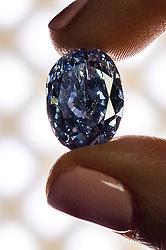 © Licensed to London News Pictures. 15/03/2016. A Sotheby's employee holds for sale from an Asian private collection, 'De Beers Millennium Jewel 4', a rare and superb Oval Internally Flawless Fancy Vivid Blue Diamond weighing 10.10 carats (Est.£21-25 million). It is one of twelve rare diamonds - eleven blue and one colourless - that form the world-renowned De Beers Millennium Jewels collection unveiled in 2000 in celebration of the millennium.  At 10.10 carats, it is the largest oval fancy vivid blue diamond ever to appear at auction.<br /> London, UK. Photo credit: Ray Tang/LNP
