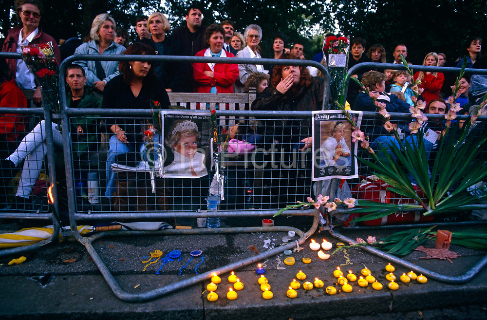 Crowds have gathered overnight before the funeral of Diana Princess of Wales – the Peoples' Princess - after her tragic car crash death in Paris. It is early morning in the Mall and families wait patiently and reverently behind police barriers lining the route where her body followed by the royal family will pass in a few hours. Tens of thousands have claimed their places for good vantage points while dressing the railings with flags and pictures and candles spelling her name along with flowers that will be thrown across the road as her cavalcade drives slowly past. Their monarchist sympathies ensure that the nation is mourning this popular lady while angry with the Queen's apparent inability to show sympathy herself.