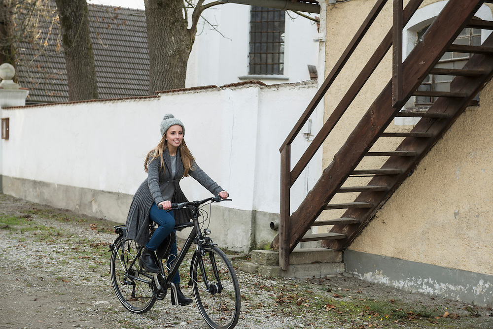 Teenager girl riding a bicycle on street, Munich, Bavaria, Germany