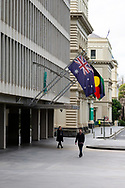 A man and a woman are seen walking under the flags at 1 Treasury Place during COVID-19. A further 238 Coronavirus cases have been discovered overnight, bringing Victoria's active cases to over 2000, speculation is rising that almost all of Victoria's current cases stem from the Andrews Government botched hotel quarantine scheme as well as the Black Lives Matter protest.  Premier Daniel Andrews warns that Victoria may go to Stage 4 lockdown if these high numbers continue. (Photo be Dave Hewison/ Speed Media)