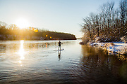 A man stand-up paddleboards (SUP) in the early winter morning in sub-freezing temperatures on a lake in eastern Pennsylvania.