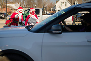 """05 DECEMBER 2020 - INDIANOLA, IOWA: STAN THOMPSON and his wife, EILEEN THOMPSON, dressed as Santa Claus and Mrs. Claus, wave to children in a car during a drive through visit with Santa Claus. This is the seventh year the Thompsons have dressed as the Clauses to entertain the children of Indianola. About 500 children visited Santa Claus and Mrs. Claus in Indianola Saturday. The town has hosted Santa on the town square for the last seven years but the COVID-19 (SARS-Cov-2) pandemic forced organizers to move the event to the parking lot of a local hardware store and do it """"drive through"""" style. Iowa has one of the highest Coronavirus test rates in the United States.      PHOTO BY JACK KURTZ"""