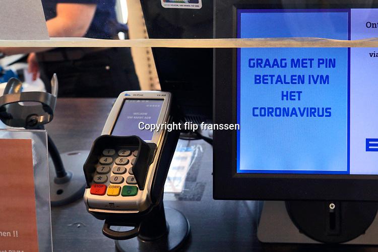 Nederland, Nijmegen, 4-5-2020 In een winkel, supermarkt, wordt de klant gevraagd alleen met pin te betalen ivm coronavirus en het besmettingsgevaar daarvan . Betaling, elektronisch,pinnen, contacloos, omzet, omzetverlies . Foto: Flip Franssen