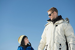 Father and son looking at each other, smiling, Bavaria, Germany
