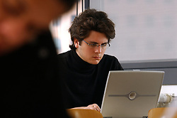 PARIS -  FRANCE - APRIL-21-2004 -Young man wearing glasses alone using a wireless - wifi - laptop computer. (PHOTO © JOCK FISTICK)..technology- business - laptop - notebook - computer - wifi - wireless - internet - communication - email - www - world wide web - web surfing - connect - connecting - connected - connectivity - study - studying - research - academics - education - student - university - young - adult - male - man - think - thinking - concentrate - concentration - concentrating