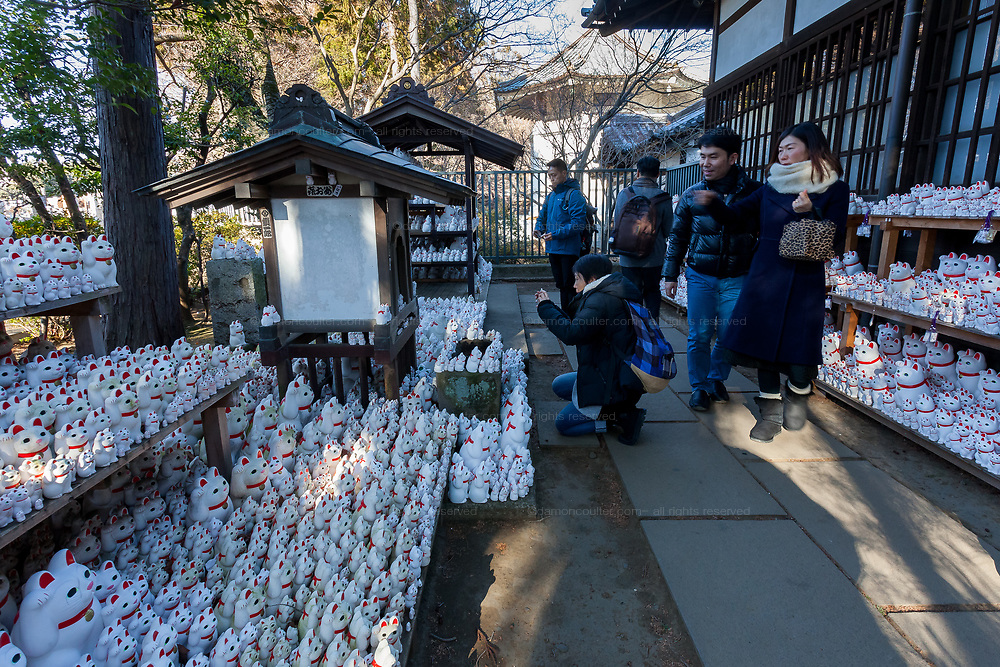 """Asian tourists take photos of the large collection of """"Lucky Cat"""" statues at Gotokuji Temple in Gotokuji, Satagaya, Tokyo, Japan. Friday January 11th 2019. Gotoikuji Temple is famous as the supposed birthplace of the """"maneki neko"""" or  """"beckoning cat"""", which is a small white cat with one paw raised that is considered a lucky charm bringing customers and money into a business."""