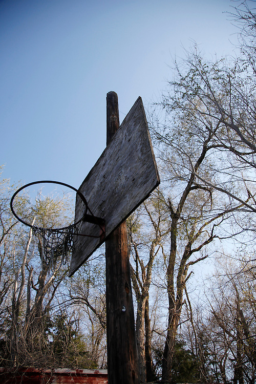 An abandoned basketball backboard and net rust in the yard of a decaying house in Monowi, Nebraska April 28, 2011. At its peak in the 1930's the town had 150 residents but after the railroad left it began to decline. Now down to a population of just one, Monowi is the only incorporated town, village or city in the United States with just a single resident.  REUTERS/Rick Wilking (UNITED STATES)