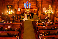 High angle interior view of a wedding ceremony, Plassen Church (kirke), a wooden (stave) church originally built in 1879. It burnt to the ground in 1904 and was rebuilt in 1907. Trysil, Norway.
