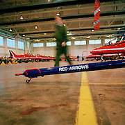 Member of the Blues, the support of the 'Red Arrows', Britain's Royal Air Force aerobatic team walks past tow-bar in hangar