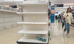 © Licensed to London News Pictures. 31/07/2021. London, UK. A shopper walks past empty shelves of bottled drink water in Sainsbury's, north London. Record breaking numbers of people have been forced to self-isolate after being alerted by the NHS Covid-19 app. The pingdemic has seen staff shortages at supermarkets, resulting in less stock making its way to supermarket shelves. Labour leader Sir Keir Starmer has demanded that the government brings forward the end to self-isolation from 16 August to 7 August. Photo credit: Dinendra Haria/LNP
