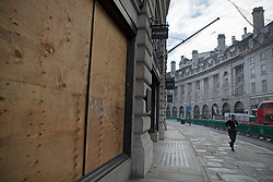 © Licensed to London News Pictures. 08/11/2020. London, UK. A man jogs past a boarded up shop on a quiet Regent Street in Central London. A national lockdown has been put in place in an attempt to fight a second wave of the COVID-19 strain of Coronavirus. Photo credit: George Cracknell Wright/LNP