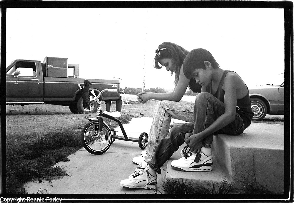 Monty Clifford puts on his new sneakers while his mother Jonnie is lost in thought on the Pine Ridge reservation in South Dakota, 1990.