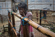 A girl gestures during torrential rain in Chakmarkul, part of the refugee camp sheltering over 800,000 Rohingya refugees, Cox's Bazar, Bangladesh, July 4, 2018. Children are the most vulnerable to waterborn diseases, and there are more than 100,000 of them at risk in the flooding.