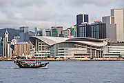 A Junk boat passes Hong Kong Convention and Exhibition Centre in Victoria Harbour Hong Kong.