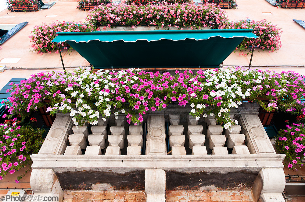 Flowers in window boxes. Known for glass making and lampworking (modern torchworking) since 1291 AD, Murano is a series of islands linked by bridges in the Venetian Lagoon, northern Italy, Europe. Venetian glass is world-renowned as colorful, elaborate, and skillfully made. Once an independent comune, Murano is now a frazione of the comune of Venice. Venice and the Venetian Lagoons are on the prestigious UNESCO World Heritage List.