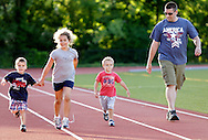 Scott Freestone, at right, watches his son Noah Freestone, 3, run on the track as Lindsay Zgrodek 7, holds the hand of her brother Evan Zgrodek during the Twilight Track Series at Middletown High School on Tuesday, July 30, 2013.