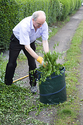 Man stuffing hedge clippings into a bin,
