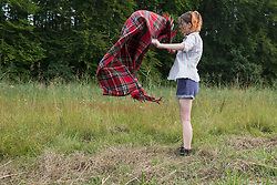 Young woman shaking blanket during camping, Bavaria, Germany