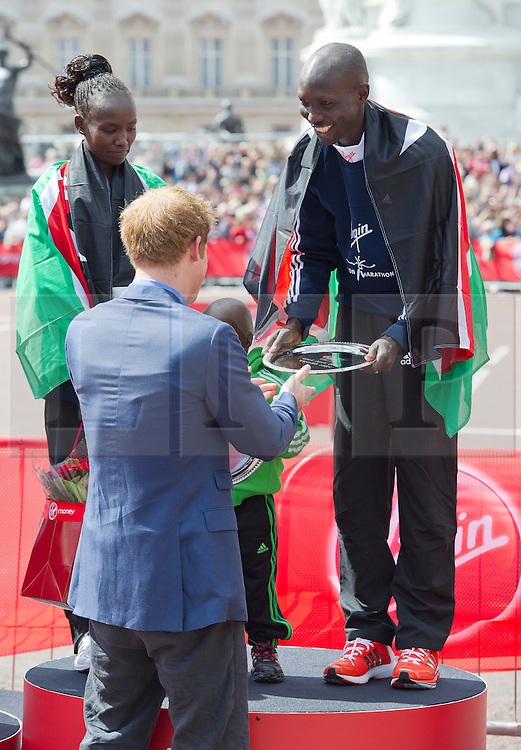 © London News Pictures. 22/04/2012. London, UK. HRH Prince Harry presenting the winners trophy to Wilson Kipsang (right) and Mary Keitany of Kenya (left)  who came first in the elite races at the 2012 Virgin London Marathon on April 22, 2012. Photo credit : Ben Cawthra /LNP