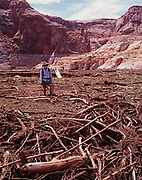 Tim Pfeiffer attempting to hike through quagmire of quick-mud and rotting vegetation clogging Navajo Canyon seven miles below the confluence with Choal Canyon, Glen Canyon National Recreation Area, Arizona.  This photo depicts sediment and debris filling Lake Powell behind the Glen Canyon Dam.  Low lake level at 3,600 feet exposes destruction of a formerly pristine riparian canyon.