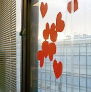 The paper hearts on the window  are the left overs of Valentine celebrations: a commercial festival in Britain  and elsewhere where people are persuaded to exchange tokens of love.From the series Desk Job a project which explores globalisation through office life around the World.