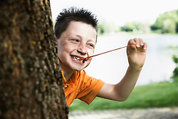 Boy pulling bubble gum and peeking out from behind a tree, Bavaria, Germany