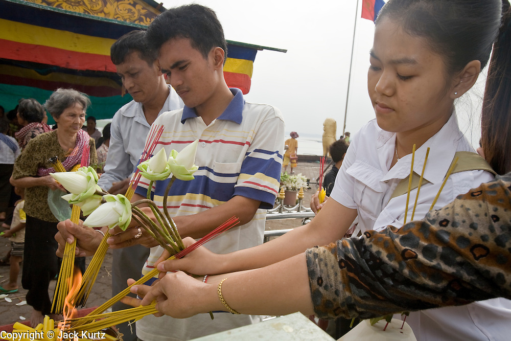 """14 MARCH 2006 - PHNOM PENH, CAMBODIA: People pray and make offerings at a small pagoda in front of the Royal Palace in Phnom Penh, Cambodia to pray. The pagoda serves as the """"spirit house"""" of the palace. The Cambodians (and Thais) build small spirit houses, which have great religious significance, in front of the homes and usually businesses. They pray at the spirit homes and frequently leave small offerings of fruit and small change in them. The spirit house for the Palace has become a public shrine and there are usually people there praying, leaving donations and lighting incense. PHOTO BY JACK KURTZ"""