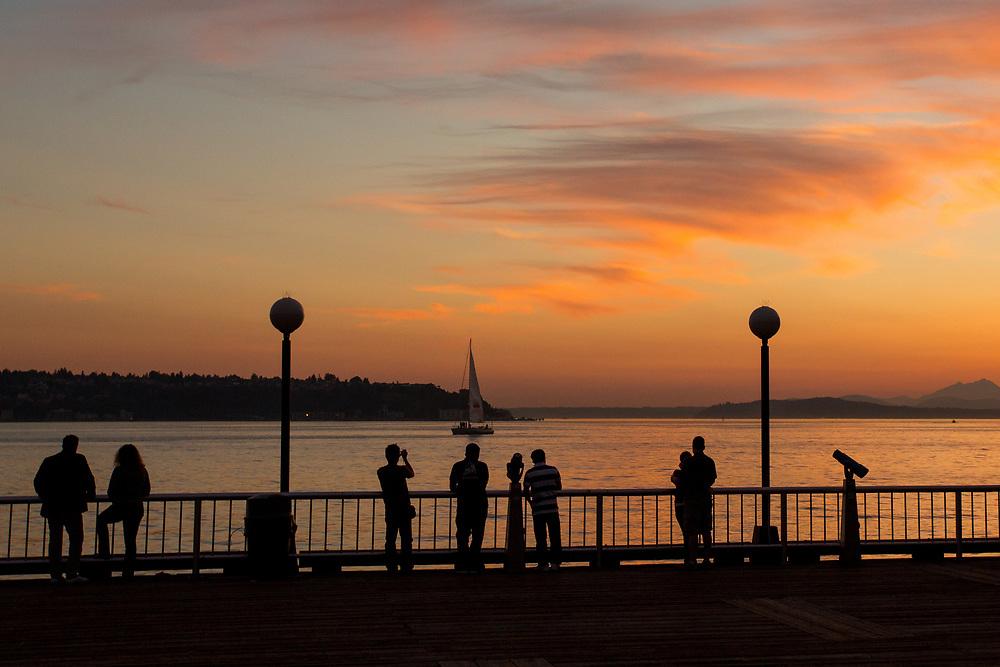 United States, Washington, Seattle, people on pier at sunset