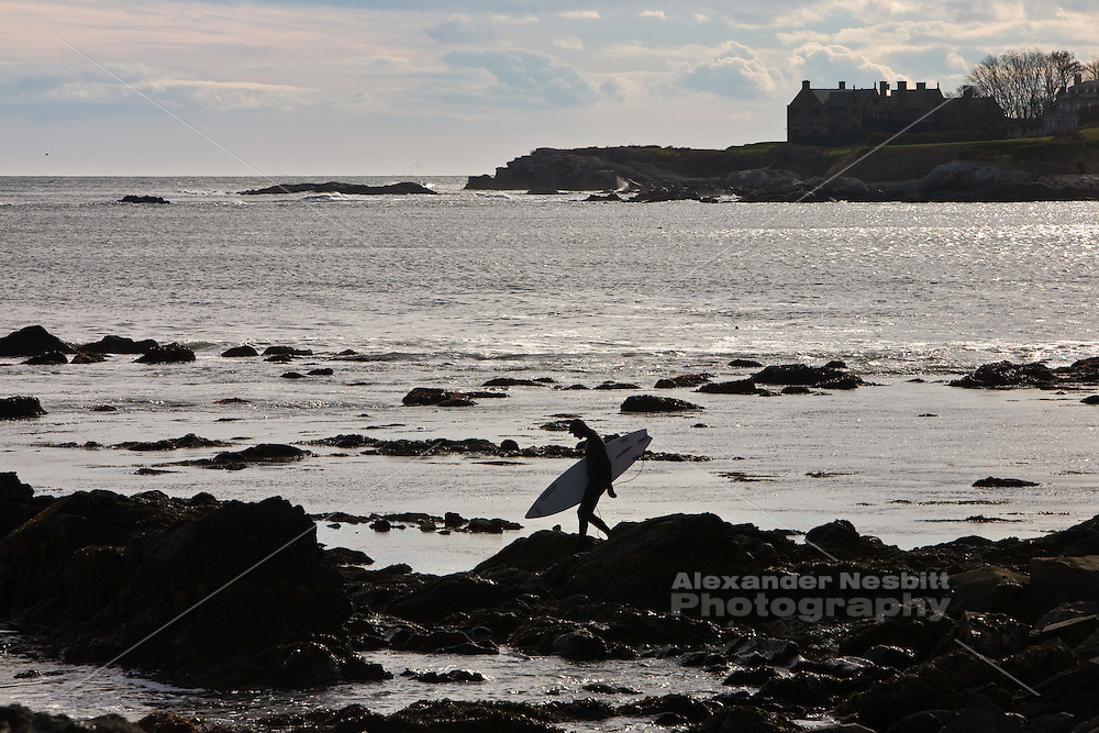 Surfer heads out to Ruggles point off the Cliff walk, Newport, RI
