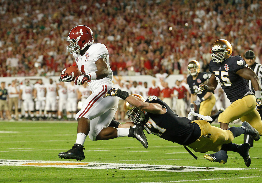 January 7, 2013:  Alabama running back T.J. Yeldon (4) runs for yardage as Notre Dame safety Zeke Motta (17) attempts to make the tackle during the Discover BCS National Championship between the Alabama Crimson Tide and the Notre Dame Fighting Irish at Sun Life Stadium in Miami Gardens, Florida.  Alabama defeated Notre Dame 42-14.