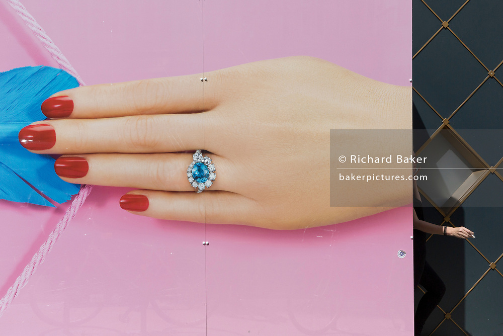 A person smokes a cigarette around the back of a temporary construction hoarding for the jewellery retailer Hirsch that features a manicured hand, painted nails and an unheated Paraíba Tourmaline ring, set with fine white diamonds designed by HIRSH, on 13th August 2019, in London England.