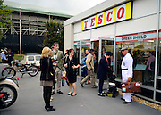 © Licensed to London News Pictures. 14/09/2012. Goodwood, UK People outside the entrance. Tesco supermarket has recreated a sixties style branch of one of it's stores at The Goodwood Revival. Customers can browse items from the period and the staff are all wearing vintage uniform. People enjoy the atmosphere at the 2012 Goodwood Revival. The event recreates the glorious days of motor racing and participants are encouraged to dress in period dress. Photo credit : Stephen Simpson/LNP