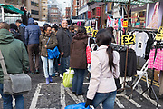 """People out shopping on Pettycoat Lane Market in the City of London, UK. Petticoat Lane Market is a fashion and clothing market in the East End of London. It consists of two adjacent street markets. Wentworth Street Market is open six days a week, and Middlesex Street Market is open on Sunday only. The name Petticoat Lane came from not only the sale of petticoats but from the fable that """"they would steal your petticoat at one end of the market and sell it back to you at the other."""""""