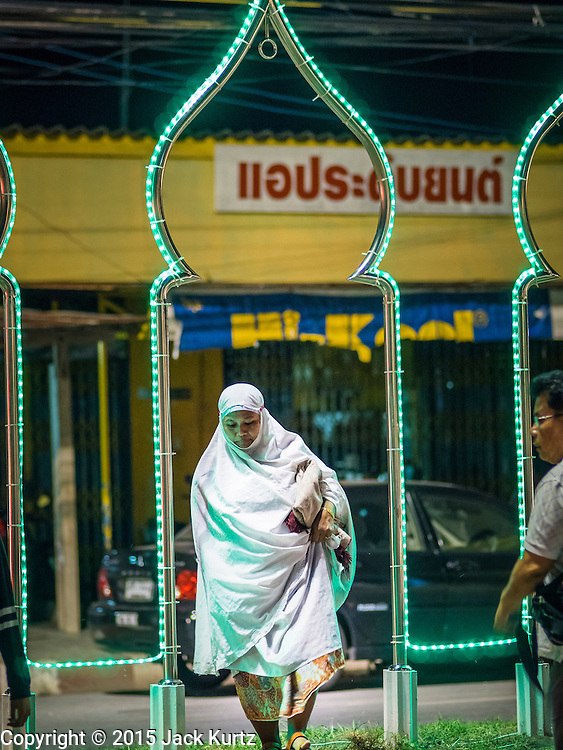 18 JUNE 2015 - PATTANI, PATTANI, THAILAND:  A woman walks under a Ramadan light display on her way to worship at Pattani Central Mosque on the first day of Ramadan. Thousands of people come to Pattani Central Mosque in Pattani, Thailand, to mark the first night of Ramadan. Ramadan is the ninth month of the Islamic calendar, and is observed by Muslims worldwide as a month of fasting to commemorate the first revelation of the Quran to Muhammad according to Islamic belief. This annual observance is regarded as one of the Five Pillars of Islam. Islam is the second largest religion in Thailand. Pattani, along with Narathiwat and Yala provinces, all on the Malaysian border, have a Muslim majority.    PHOTO BY JACK KURTZ