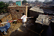A performer practices his tightrope walking (or high-wire) act in the slums of Shadipur.<br /> The Kathiputli Colony in the Shadipur Depot slum is home to hundreds of (originally Rajasthani) performers. The artistes who live here - from magicians, acrobats, musicians, dancers and puppeteers are often international renowed by always return to the Shadipur slum.