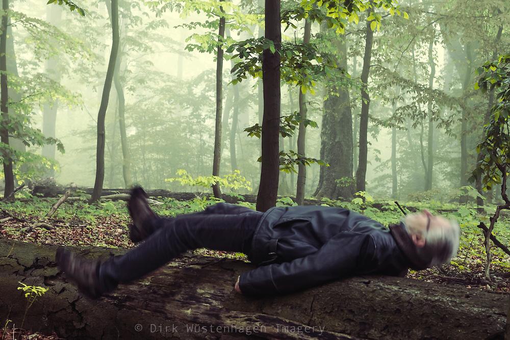 Mann legt sich auf Baumstamm (Bewegungsunschärfe) Wuppertal, Deutschland