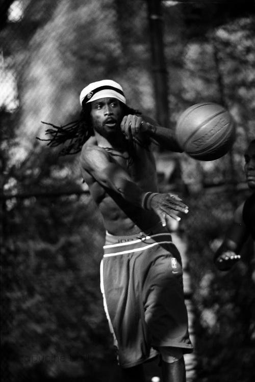April 24th 2004. New York, New York. United States..Located in the heart of Greenwich Village, the West 4th Street basketball Court, known as ?The Cage?, offers no seating but attracts the best players and a lot of spectators as soon as spring is around the corner..Half the size of a regular basketball court, it creates a fast, high level of play. The more people watch, the more intense the games get. « The Cage » is a free show. Amazing actions, insults and fights sometimes, create tensions among and inside the teams. The strongest impose their rules. Charisma is present..?The Cage? is a microcosm. It?s a meeting point for the African American street culture of New York. Often originally from Jamaica or other islands of the Caribbean, they hang out, talk, joke, laugh, comment the game, smoke? Whether they play or not, they?re here, inside ?The Cage?. Everybody knows everybody, they all greet each other, they shake hands and hug: ?Yo, whasup man??.