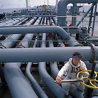 USA, Alaska, Second mate Karen Devine checks valves aboard Oil tanker Arco Juneau sailing for San Francisco, CA