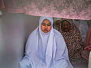 06 JULY 2016 - BANGKOK, THAILAND: Women pray during Eid services at Bang Luang Mosque in the Thonburi section of Bangkok. Eid al-Fitr is also called Feast of Breaking the Fast, the Sugar Feast, Bayram (Bajram), the Sweet Festival or Hari Raya Puasa and the Lesser Eid. It is an important Muslim religious holiday that marks the end of Ramadan, the Islamic holy month of fasting. Muslims are not allowed to fast on Eid. The holiday celebrates the conclusion of the 29 or 30 days of dawn-to-sunset fasting Muslims do during the month of Ramadan. Islam is the second largest religion in Thailand. Government sources say about 5% of Thais are Muslim, many in the Muslim community say the number is closer to 10%.        PHOTO BY JACK KURTZ