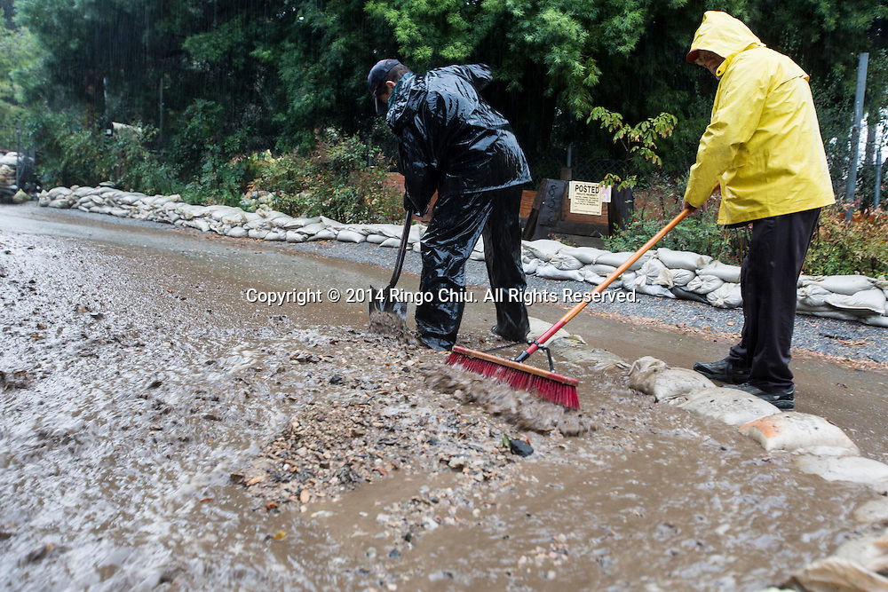 People work to stem mud and debris flowing down a hillside from the burnt areas in Glendora, California, Tuesday, December 2, 2014. The rain, along with gusty winds, is the result of a Pacific storm system. Forecasters said the storm should drop about 1 to 2 inches of rain along the coast and in valley areas, and 2 to 5 inches in the mountains and foothills.(Photo by Ringo Chiu/PHOTOFORMULA.com)