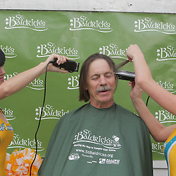 12 March 2009: Two New Orleans Hornets Honeybee NBA dancers shave the head of a participant during the annual St. Baldrick's charity fund raiser held at Parasol's Bar in the Irish Channel of New Orleans, Louisiana.