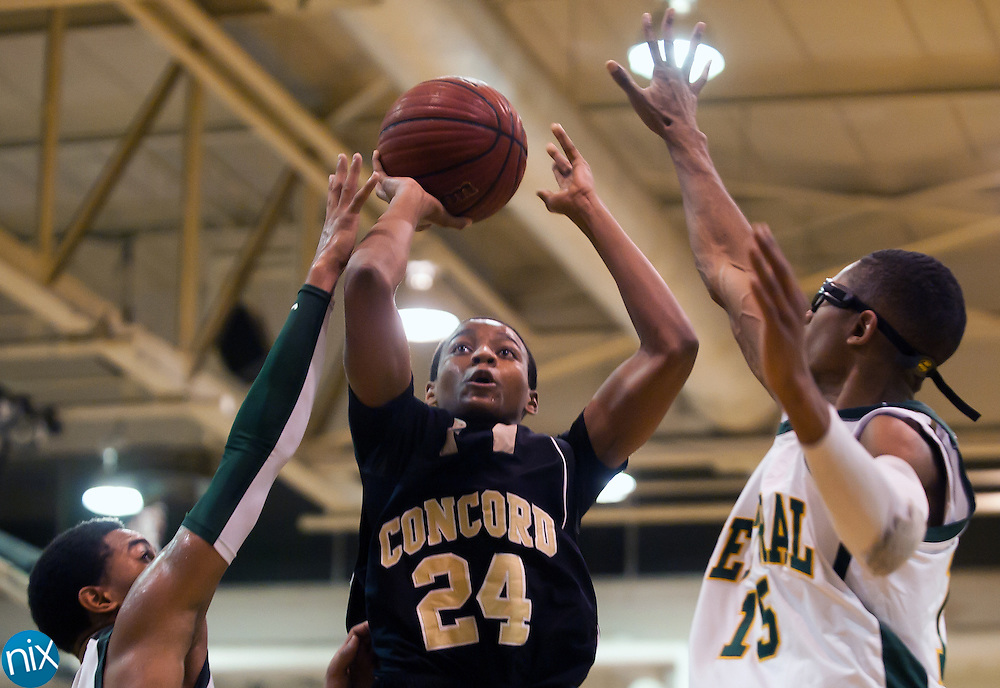 Concord's Darren Black goes up for a shot against Central's L.C. Cooks and Xavier Deer Tuesday night at Central Cabarrus High School in Concord. The Spiders won the South Piedmont Conference matchup 82-75.  (Photo by James Nix)
