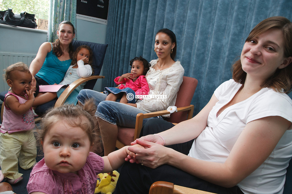 Young mothers and children in discussion group.