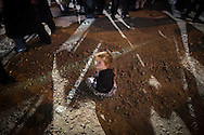 A small child sit in the dust at late night during the Lag BaOmer celebrations in the orthodox distric of Mea Shearim
