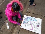 "22 APRIL 2016 - MINNEAPOLIS, MN: MINA LEIERWOOD, from Minneapolis, MN, brings a thank you card to the memorial for Prince at 1st Ave in Minneapolis. She said she listened to Prince's music all through high school. Thousands of people came to 1st Ave in Minneapolis Friday to mourn the death of Prince, whose full name is Prince Rogers Nelson. 1st Ave is the nightclub the musical icon made famous in his semi autobiographical movie ""Purple Rain."" Prince, 57 years old, died Thursday, April 21, 2016, at Paisley Park, his home, office and recording complex in Chanhassen, MN.    PHOTO BY JACK KURTZ"