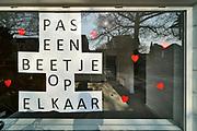 Nederland, Nijmegen, 12-4-2020 Achter het raam van een kantoor is de tekst Let Een Beetje Op Elkaar samen met rode hartjes opgehangen als dank en respectbetuiging aan het personeel in de zorg en op de ic die met het coronavirus te maken hebben . Foto: Flip Franssen