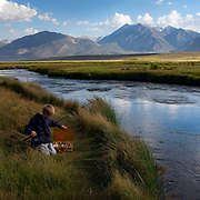 A young teenager and his tackle box at the Owens River near Benton Crossing in the Eastern Sierras.