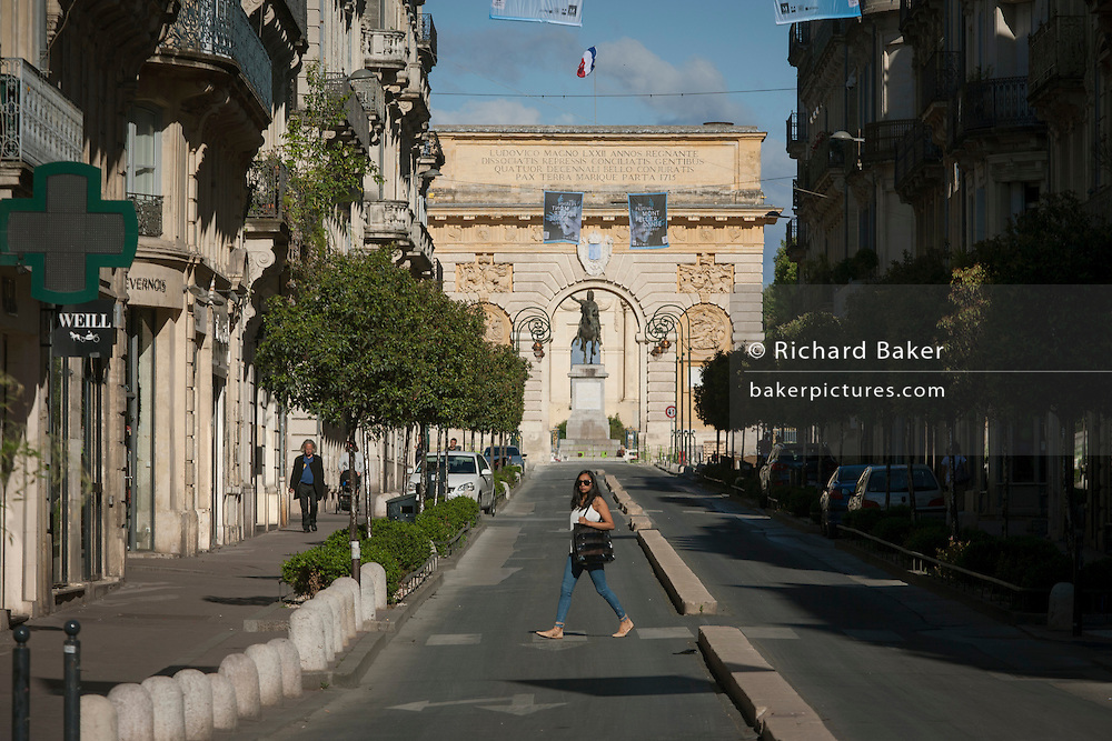Local lady crosses Rue Foch in front of the 17th century Arc de Triomphe in Montpellier, south of France.